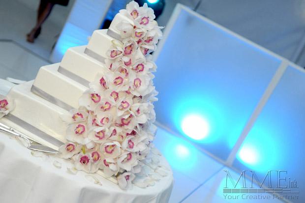 White wedding cake design with flowers framed by lighting backdrop